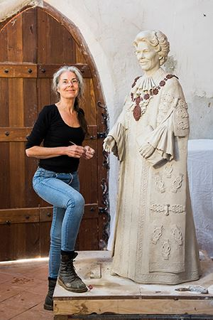 Sculptor Margot Stephens with her as-yet unfinished statue of Joy Cummings.