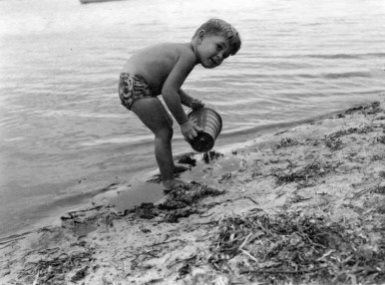 Little boy with a sand bucket by the lake