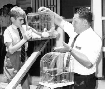 Mr. Robert Garside passing Birds in cages to a boy