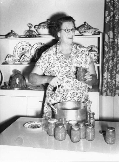 Florence Austral in a kitchen with canned preserves