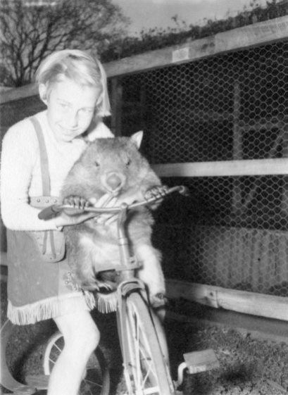 Young girl holding a wombat on a bicycle