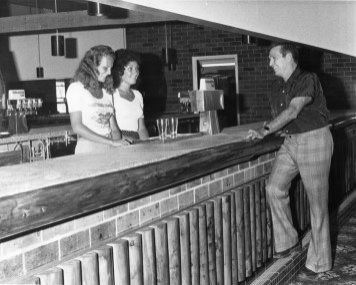 Man leaning at bar chatting with 2 female bartenders