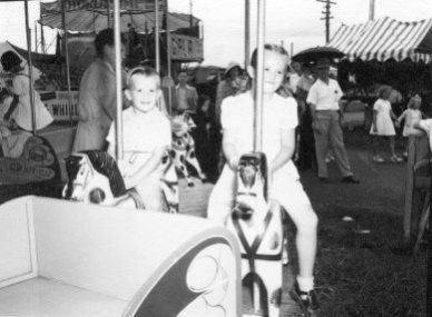 Children riding merry-go-round horses at the Newcastle Show