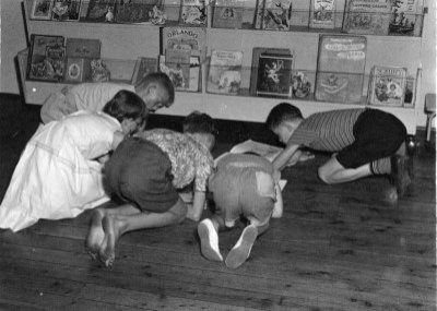 Children in library reading books on the floor