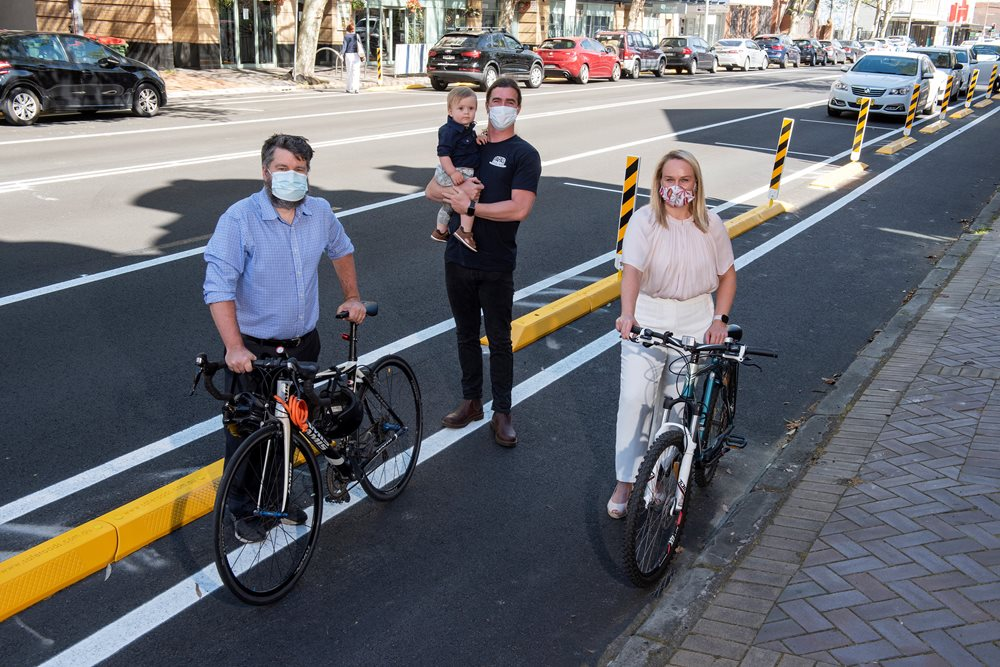 Councillor John Mackenzie, Papa's Bagel Bar's Johno Quinn with son Elijah, and Lord Mayor Nuatali Nelmes on Hunter Street at the location of the new Hunter Street Trial Cycleway.