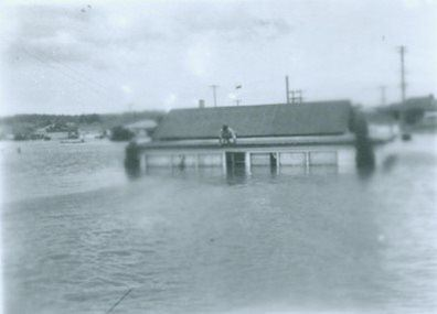 Man sitting on house in Maitland flood 1950